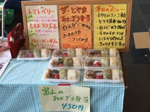 シロエビの天ぷらとホタルイカの唐揚げを添えた自慢の「富山のおにぎり弁当」と商品説明ポップ