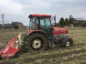トラクターは、土を起こす耕起に続き、土と水を撹拌する作業の「あらくり」中